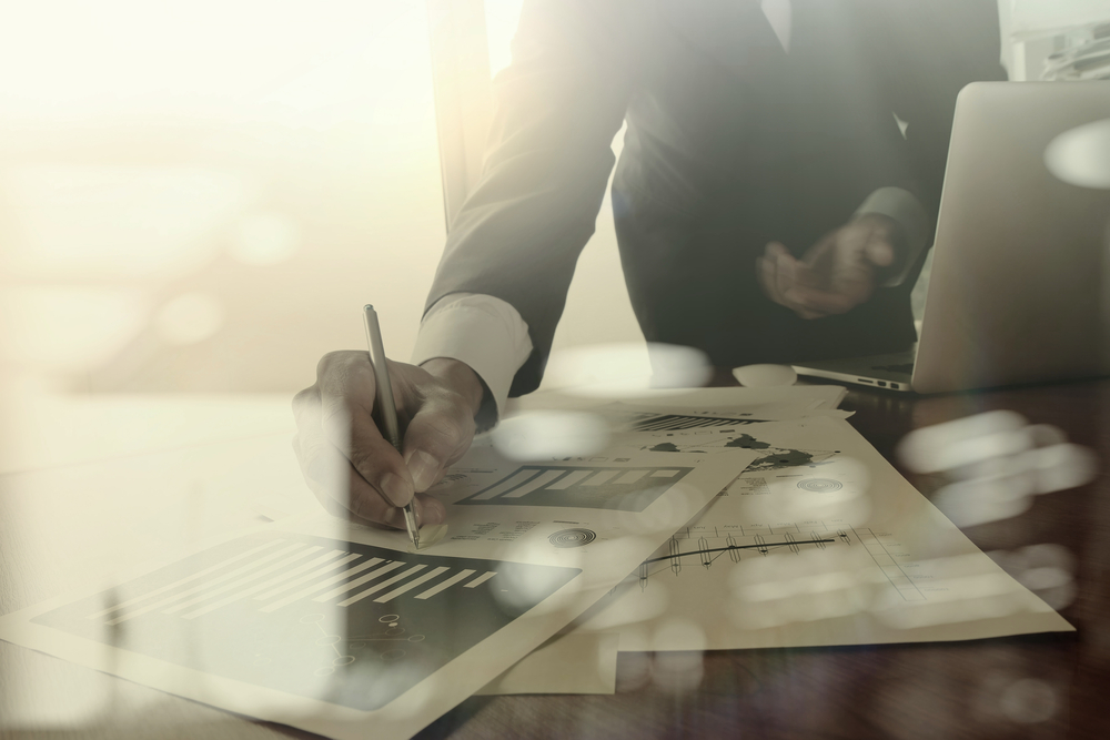 business documents on office table with smart phone and digital tablet and graph business diagram and man working in the background-1